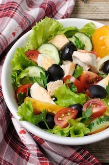 Sałatka jarzynowa z kurczakiem i oliwkami z jajek w liściach sałaty pionowo ujęta