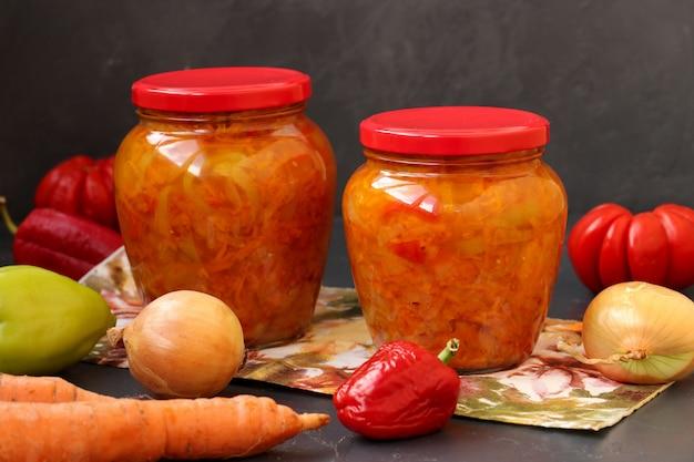 Sałatka jarzynowa z marchwi, papryki, cebuli i pomidorów na zimę znajduje się na stole na ciemnym tle