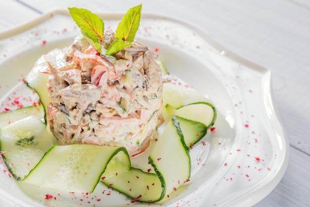 Sałatka jarzynowa z mięsem, ziołami, ogórkiem i przyprawami na białym talerzu