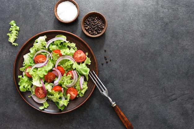 Sałatka jarzynowa z pomidorami, czerwoną cebulą i sosem na czarno, widok z góry