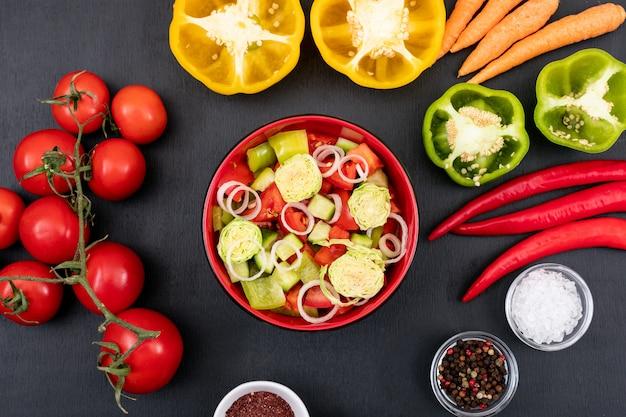 Sałatka jarzynowa z pomidorami marchewkowymi czerwona cebula żółta słodka papryka na czarnej powierzchni