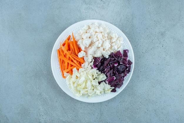 Sałatka jarzynowa z posiekaną białą i fioletową kapustą oraz dodatkami.