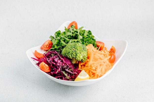 Sałatka jarzynowa z posiekaną kapustą, marchewką, plasterkami pomidorów, sałatą i brokułami.