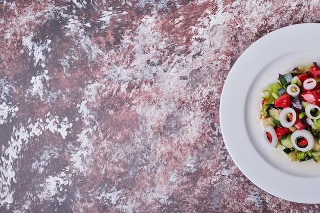 Sałatka jarzynowa z posiekanymi i mielonymi składnikami na białym talerzu, widok z góry.