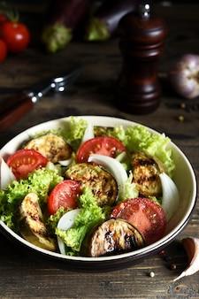 Sałatka jarzynowa z sałatą, pomidorami i grillowanymi bakłażanami na kuchennym stole.