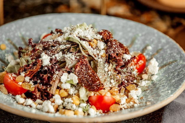 Sałatka jarzynowa z sałatą, suszonymi pomidorami, kozim serem, rodzynkami, pomidorkami cherry