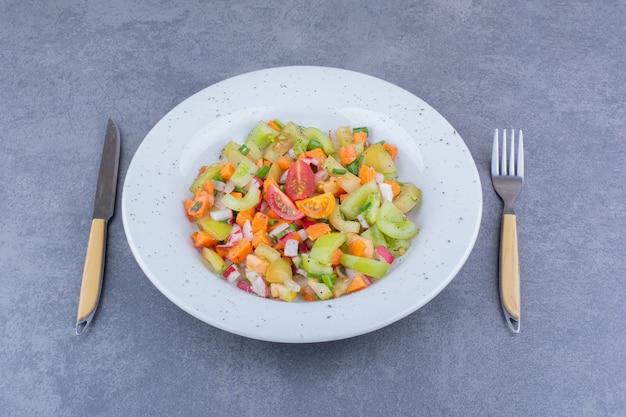 Sałatka jarzynowa z sezonowymi potrawami w ceramicznym naczyniu