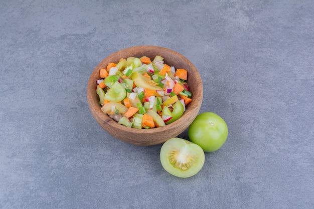 Sałatka jarzynowa z sezonowymi potrawami w drewnianym naczyniu