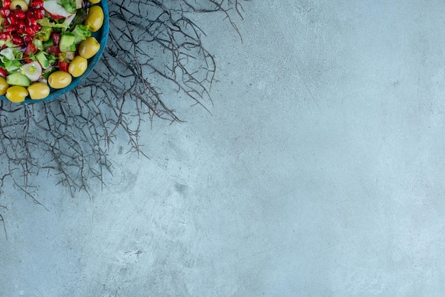 Sałatka jarzynowa z siekaną sałatą i zielonymi oliwkami.