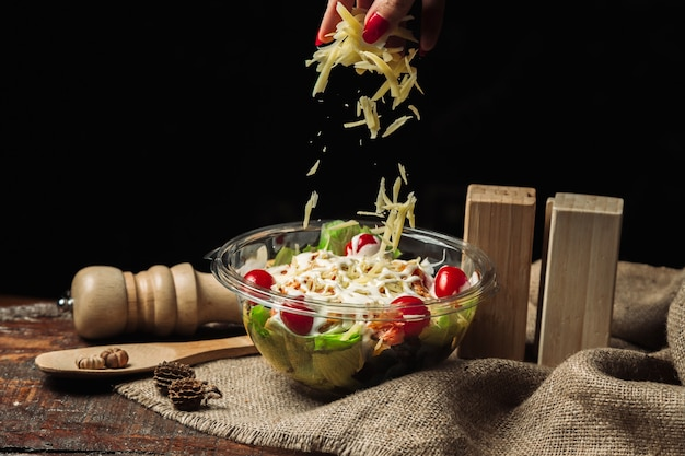 Sałatka jarzynowa z tartym serem i pomidorami doprawiona majonezem