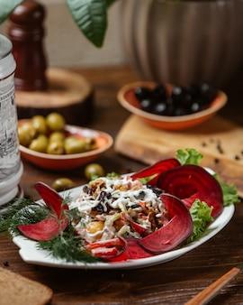 Sałatka jarzynowa ze śliwek, marchewki, pomidora, orzecha włoskiego przyozdobiona plasterkami buraków
