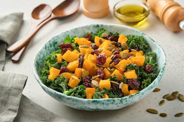 Sałatka jesienna z jarmużem, pieczoną dynią, pestkami i suszoną żurawiną w misce.