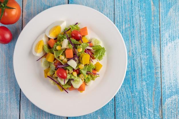 Sałatka jest na białym talerzu z kanapką i pomidorami na niebieskiej drewnianej podłodze.