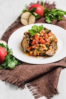 Sałatka letnia z bakłażana i pomidorów na białym talerzu