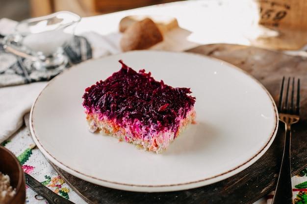 Sałatka majonezowa z pokrojonymi buraczanymi purpurowymi warzywami, solonym pieprzem z kurczaka w białej płytce
