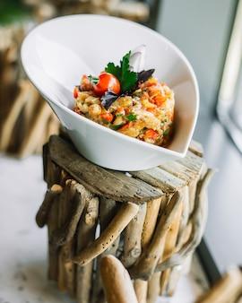 Sałatka mangal w misce na pniu oberżyny pomidor pieprz pieprz czosnek cebula widok z boku