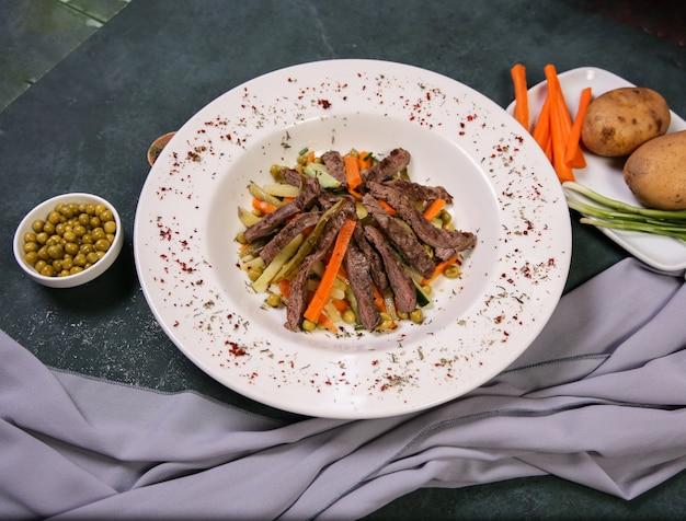 Sałatka mięsna i jarzynowa na białym talerzu.