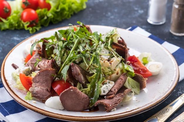 Sałatka mięsna pieczeń wołowa, warzywa i ser na talerzu. sałatka z pieczonej wołowiny.