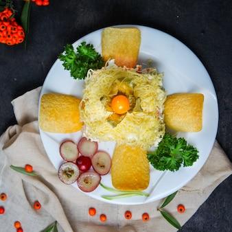 Sałatka mimosa z frytkami, owocami, ziołami w talerzu