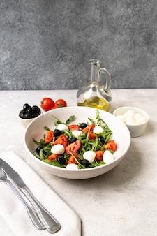 Sałatka mozzarella z pomidorami, czarnymi oliwkami, rukolą i oliwą. danie włoskiej kuchni greckiej