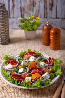Sałatka na ciepło z dynią, serem feta, suszonymi pomidorami, oliwkami, rukolą i czerwoną cebulą. zbliżenie.