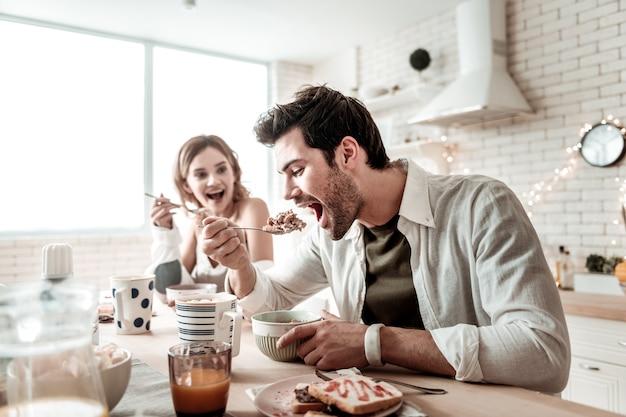 Sałatka na śniadanie. brodaty przystojny pozytywny mężczyzna ubrany w białą koszulę, jedzenie sałatki na śniadanie