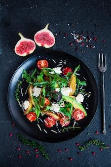 Sałatka na talerzu: rukola, pomidorki koktajlowe, białe figi, tarty ser, czarne winogrona