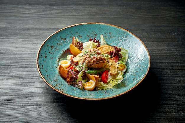 Sałatka nicejska z tuńczykiem i ziemniakami w niebieskim talerzu na drewnianym tle