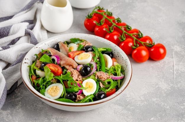 Sałatka nicejska z tuńczykiem, jajkiem, fasolką szparagową, pomidorami, oliwkami, sałatą, cebulą i anchois