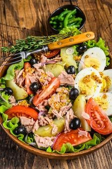 Sałatka nicejska z tuńczykiem, pomidorami, oliwkami, fasolką szparagową, ogórkiem, jajkiem na miękko i ziemniakami w drewnianej misce.