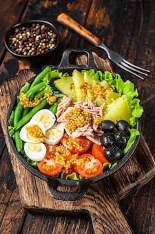 Sałatka nicejska z tuńczykiem, pomidorkami koktajlowymi, oliwkami, fasolką szparagową, ogórkiem, jajkiem na miękko i ziemniakami. ciemne tło drewniane. widok z góry.