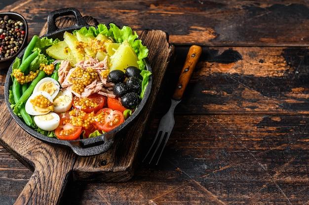 Sałatka nicejska z tuńczykiem, pomidorkami koktajlowymi, oliwkami, fasolką szparagową, ogórkiem, jajkiem na miękko i ziemniakami. ciemny drewniany stół. widok z góry.