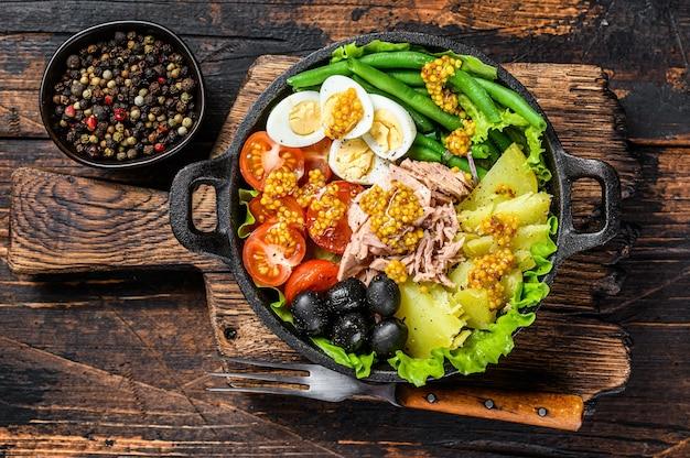 Sałatka nicejska z tuńczykiem, pomidorkami koktajlowymi, oliwkami, fasolką szparagową, ogórkiem, jajkiem na miękko i ziemniakiem. ciemne drewniane tło. widok z góry.