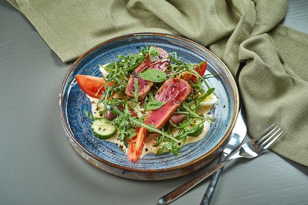 Sałatka nicoise ze świeżymi pomidorami, szparagami, papryką chili, oliwkami, jajkami przepiórczymi i smażonym tuńczykiem. tradycyjna francuska sałatka. grillowana sałatka z tuńczyka