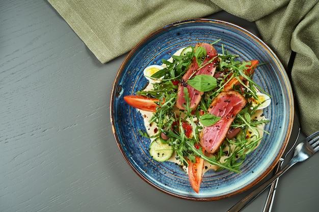 Sałatka nicoise ze świeżymi pomidorami, szparagami, papryką chili, oliwkami, jajkami przepiórczymi i smażonym tuńczykiem. tradycyjna francuska sałatka. widok z góry, miejsce