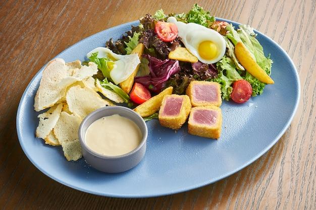 Sałatka nicoise ze świeżymi pomidorami, szparagami, papryką chili, oliwkami, jajkami przepiórczymi i smażonym tuńczykiem.