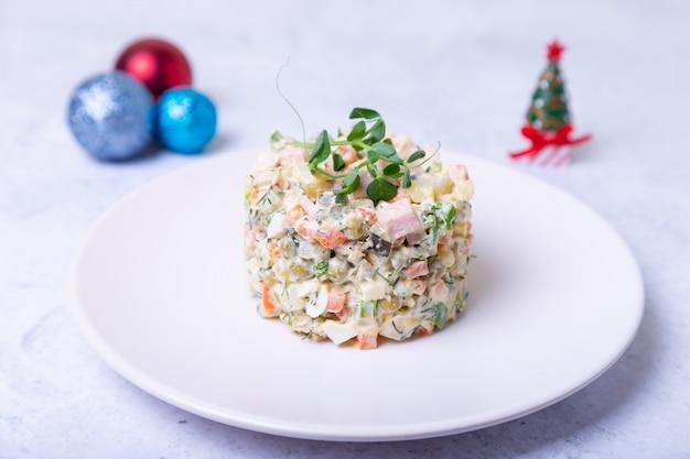 Sałatka olivier na białym talerzu, ozdobiona kiełkami grochu. tradycyjna rosyjska sałatka noworoczna i świąteczna. zakończenie, selekcyjna ostrość, biały tło.