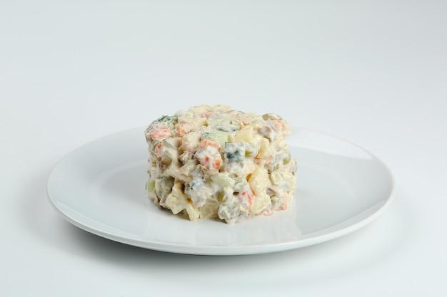 Sałatka olivier na białym talerzu. wegańska wersja tradycyjnej rosyjskiej sałatki olivier z gotowanych warzyw.