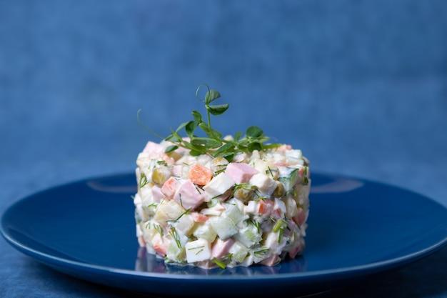 Sałatka olivier na niebieskim talerzu ozdobiona kiełkami grochu. tradycyjna rosyjska sałatka noworoczna i świąteczna. zakończenie, selekcyjna ostrość, błękitny tło.