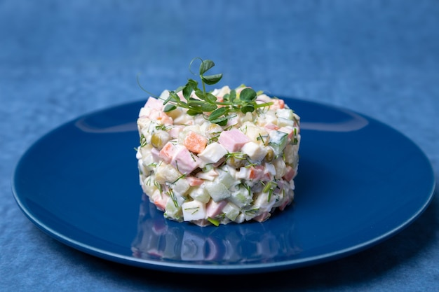 Sałatka olivier na niebieskim talerzu ozdobiona kiełkami groszku. tradycyjna rosyjska sałatka noworoczna i bożonarodzeniowa. zbliżenie,