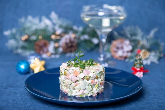 Sałatka olivier na niebieskim talerzu ozdobiona kiełkami groszku. tradycyjna rosyjska sałatka noworoczna i bożonarodzeniowa.