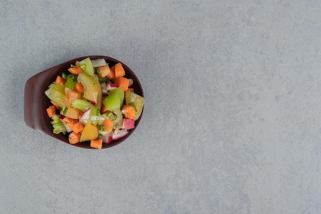 Sałatka owocowa w brązowej filiżance na betonowym stole.