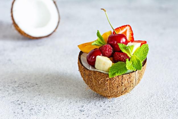 Sałatka owocowa w misce pół kokosa na szarej powierzchni