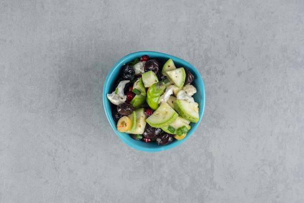 Sałatka owocowa w niebieskim kubku z czarnymi oliwkami.