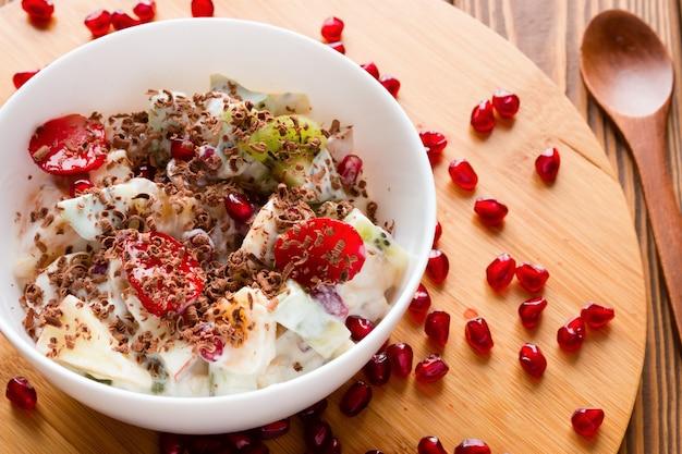 Sałatka owocowa w plasterkach, wypełniona lodami i posypana czekoladą