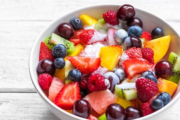 Sałatka owocowa z jogurtem, arbuzem, truskawką, wiśnią, jagodą, kiwi, malinami i brzoskwiniami w misce. zdrowe jedzenie