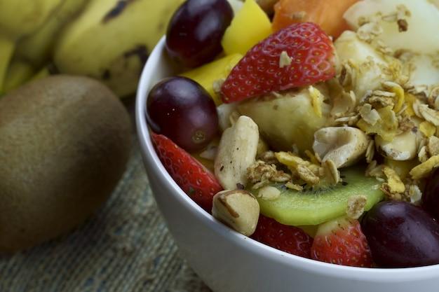 Sałatka owocowa z kasztanami i muesli w misce dojrzałe owoce ananas mango winogrona truskawka papaja