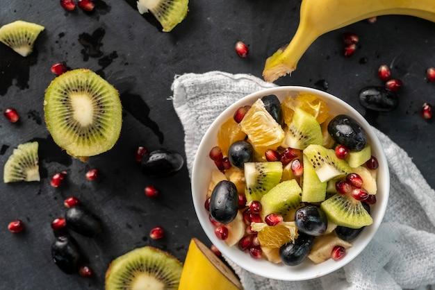 Sałatka owocowa z tropikalnymi egzotycznymi dojrzałymi owocami pokrojonymi w kostkę, pomarańczą, kiwi, bananem, winogronami, granatami