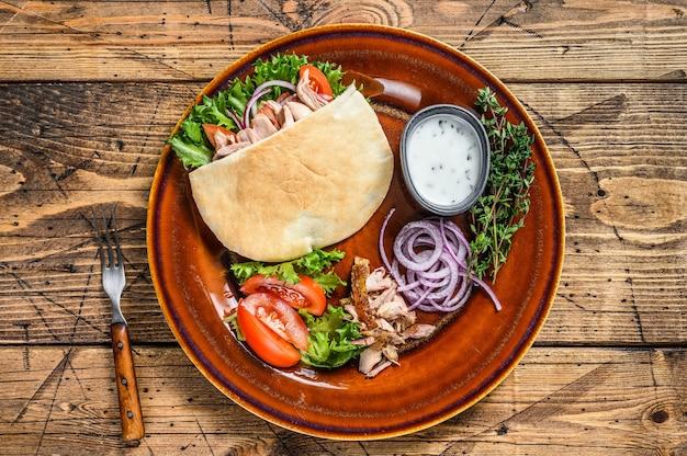 Sałatka pita z pieczonym kurczakiem i warzywami na talerzu na drewnianym stole. widok z góry.