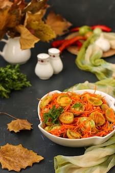 Sałatka po koreańsku z zielonymi pomidorami i marchewką w białej salaterce na ciemnym tle, pionowe zdjęcie